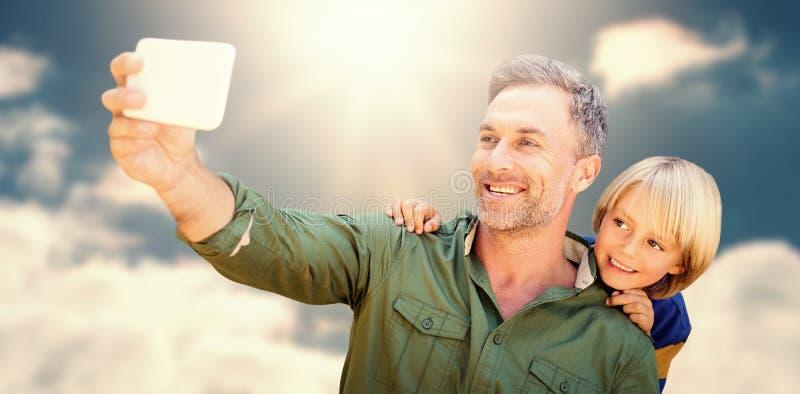 Immagine composita del padre che prende un selfie mentre tenendo suo figlio fotografia stock libera da diritti
