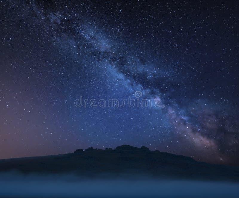 Immagine composita del paesaggio della Via Lattea vibrante di stordimento sopra i tor nei picchi rivelanti di Dartmoor attraverso fotografie stock
