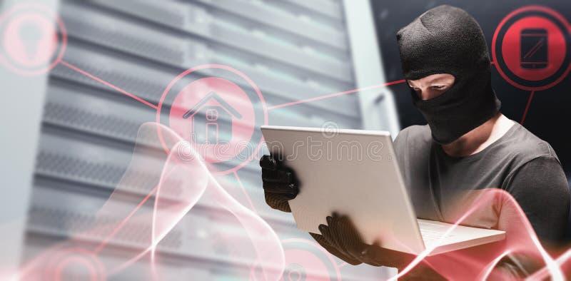Immagine composita del pirata informatico che per mezzo del computer portatile per rubare identità fotografie stock