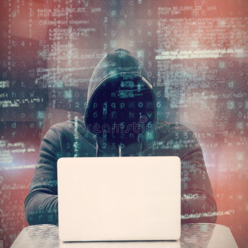 Immagine composita del pirata informatico maschio messo a fuoco che per mezzo del computer portatile fotografie stock libere da diritti