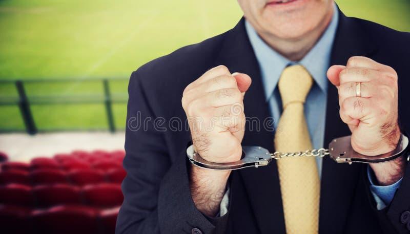 Immagine composita del primo piano dell'uomo d'affari con le mani ammanettate immagini stock libere da diritti