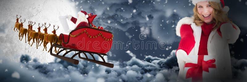 Immagine composita del regalo biondo festivo e di indicare di natale della tenuta il suo dito immagine stock