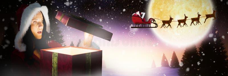 Immagine composita del regalo di Natale sorpreso di apertura della donna fotografia stock libera da diritti