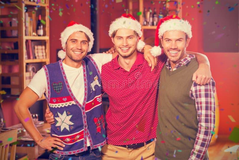 Immagine composita del ritratto degli amici con i cappelli di natale fotografie stock