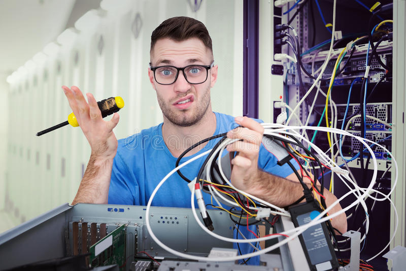 Immagine composita del ritratto del professionista IT confuso con il cacciavite ed i cavi davanti a ope immagini stock libere da diritti