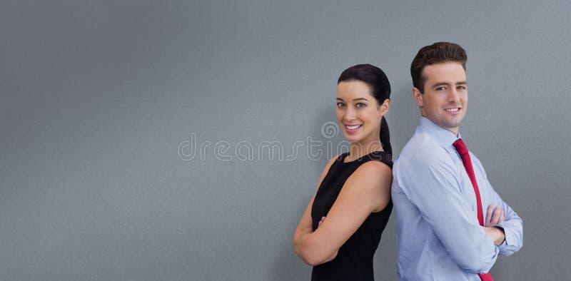 Immagine composita del ritratto dell'uomo di affari e della donna di affari che posano indietro contro la parte posteriore fotografia stock libera da diritti