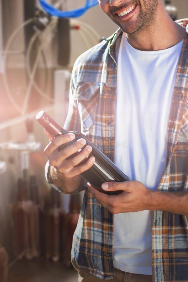 Immagine composita del ritratto della bottiglia di vino sorridente della tenuta del giovane immagini stock libere da diritti