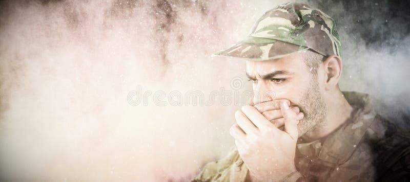 Immagine composita del soldato che copre il suo bocca fotografia stock