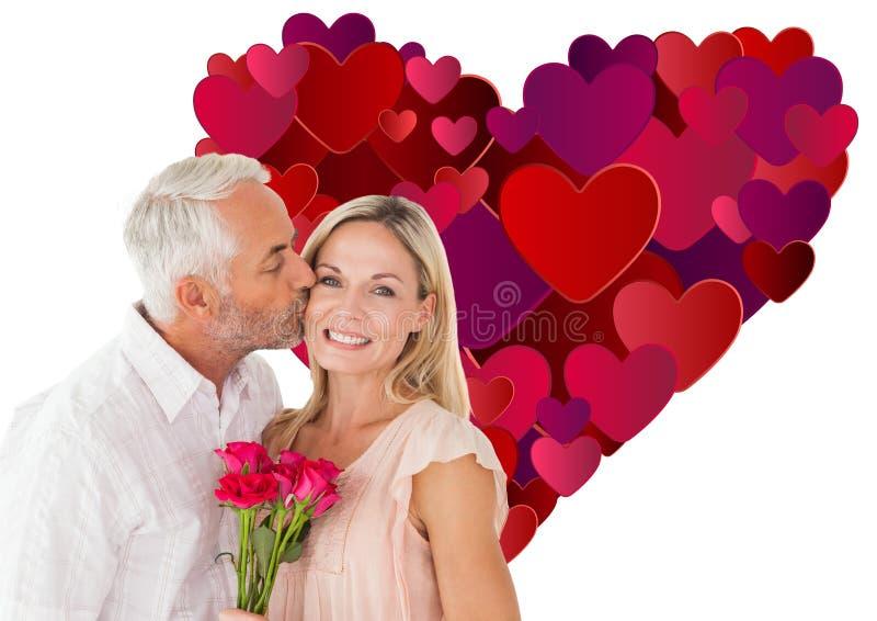 Immagine composita dell'uomo affettuoso che bacia la sua moglie sulla guancia con le rose immagini stock libere da diritti