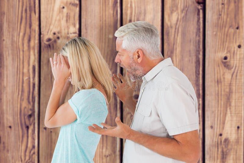 Immagine composita dell'uomo arrabbiato che grida alla sua moglie fotografia stock