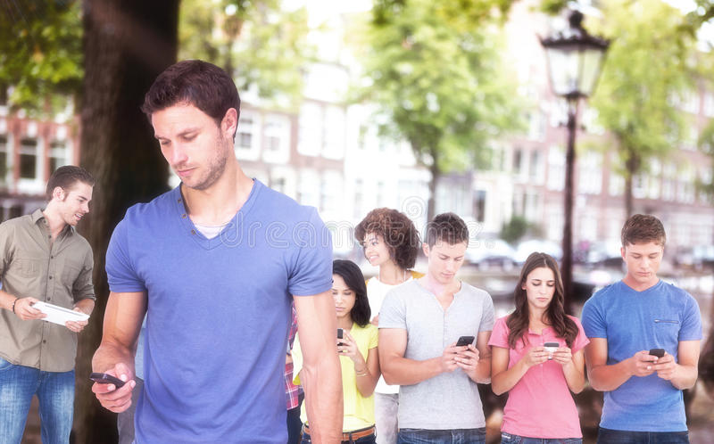 Immagine composita dell'uomo che per mezzo del suo telefono cellulare immagine stock libera da diritti