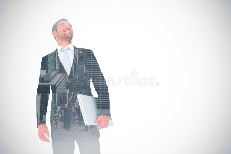 Immagine composita dell'uomo d'affari che cerca il computer portatile della tenuta fotografia stock