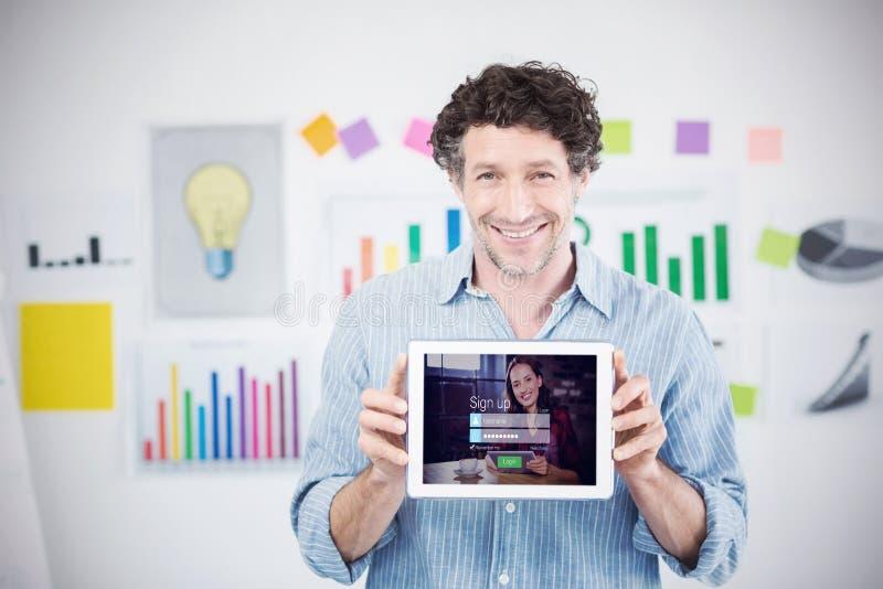 Immagine composita dell'uomo d'affari che mostra compressa digitale con lo schermo in bianco nell'ufficio creativo fotografia stock libera da diritti