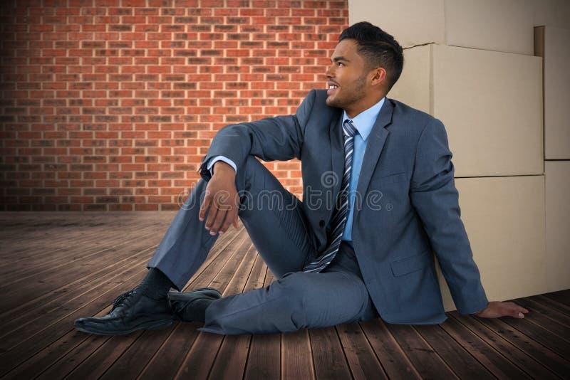 Immagine composita dell'uomo d'affari che si siede vicino alle scatole di cartone contro il fondo bianco fotografia stock