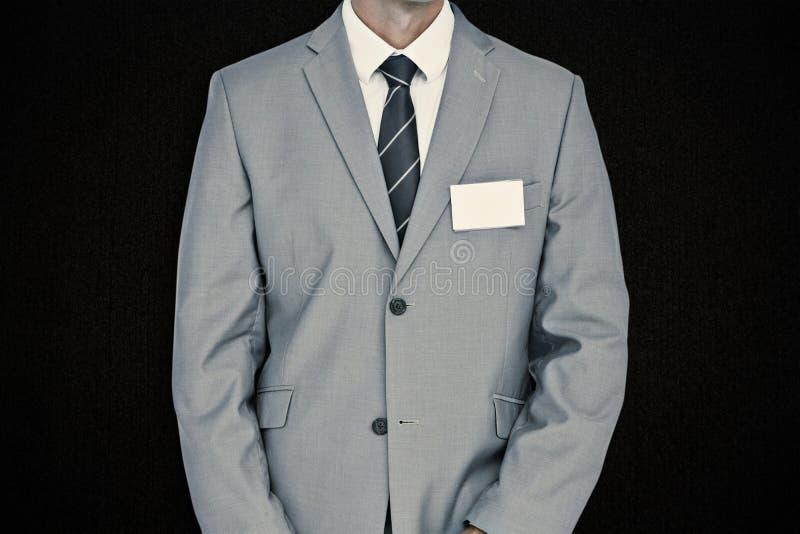 Immagine composita dell'uomo d'affari con il distintivo fotografia stock libera da diritti