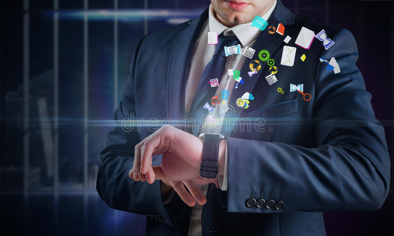 Immagine composita dell'uomo d'affari facendo uso dell'orologio dell'ologramma fotografie stock