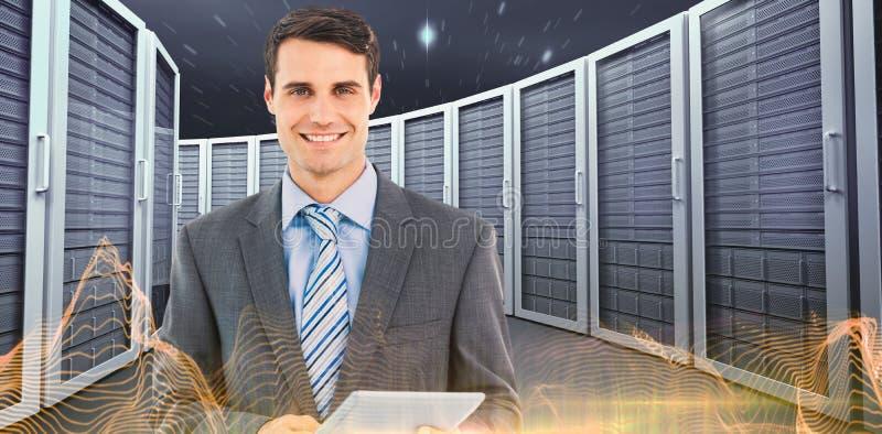 Immagine composita dell'uomo d'affari facendo uso di una compressa con i colleghi dietro in ufficio fotografie stock