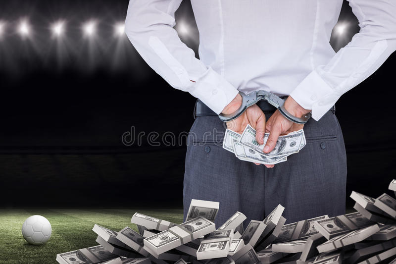 Immagine composita dell'uomo d'affari in manette che tengono dono fotografia stock