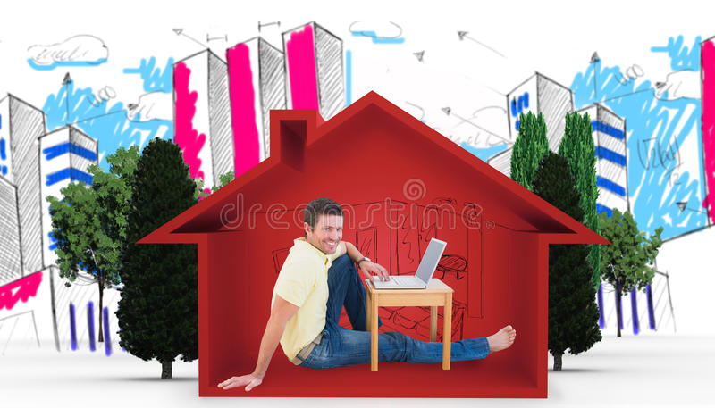 Immagine composita dell'uomo sorridente che per mezzo di un computer portatile immagine stock