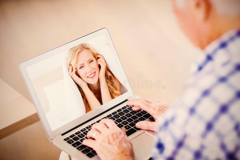 Immagine composita della bionda sveglia che sorride sotto il piumino fotografie stock