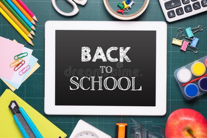 Immagine composita della compressa digitale sullo scrittorio con di nuovo alla scuola me fotografia stock libera da diritti