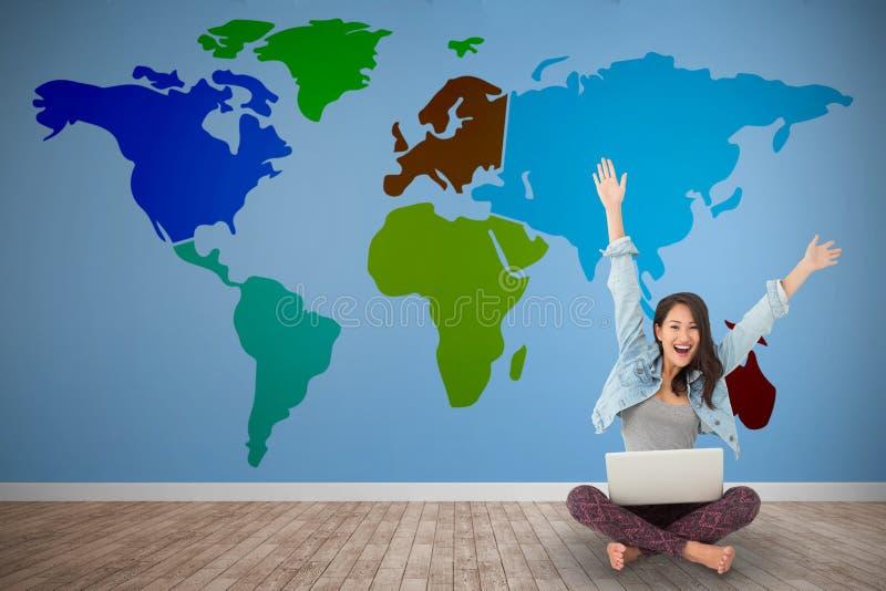 Immagine composita della donna asiatica che incoraggia alla macchina fotografica con il computer portatile che si siede sul pavim fotografie stock libere da diritti