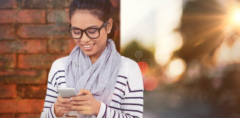 Immagine composita della donna asiatica sorridente che per mezzo dello smartphone fotografie stock libere da diritti