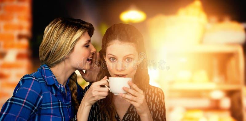 Immagine composita della donna che bisbiglia nell'altro orecchio della donna mentre avendo una tazza di caffè fotografie stock