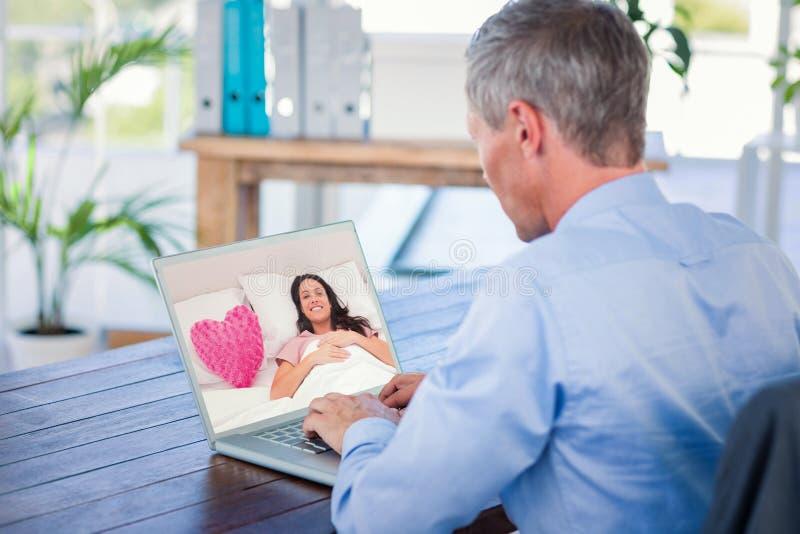 Immagine composita della donna che si trova nel suo letto accanto ad un cuscino rosa del cuore fotografie stock