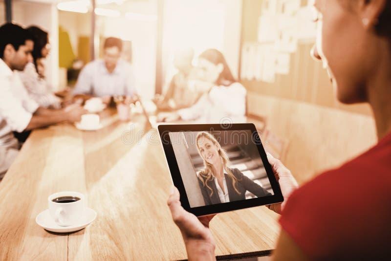 Immagine composita della donna che tiene compressa digitale con i colleghi nel fondo fotografia stock libera da diritti