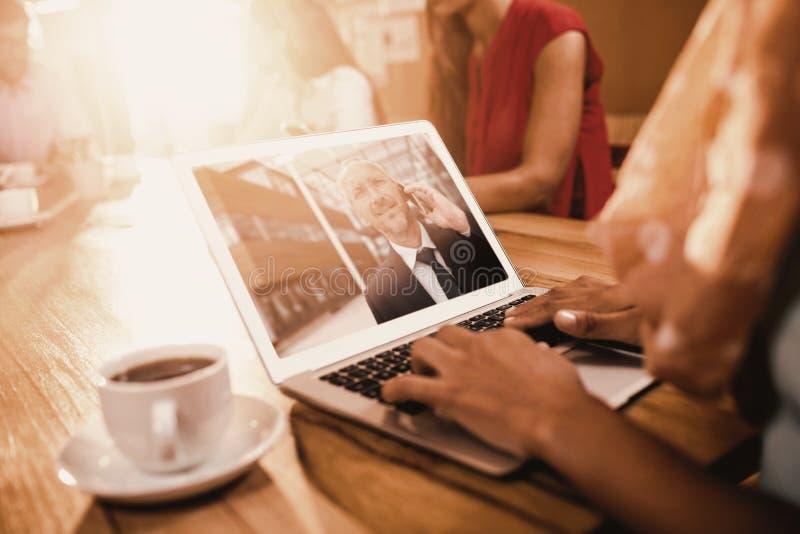 Immagine composita della donna di affari che lavora al computer portatile all'ufficio fotografia stock