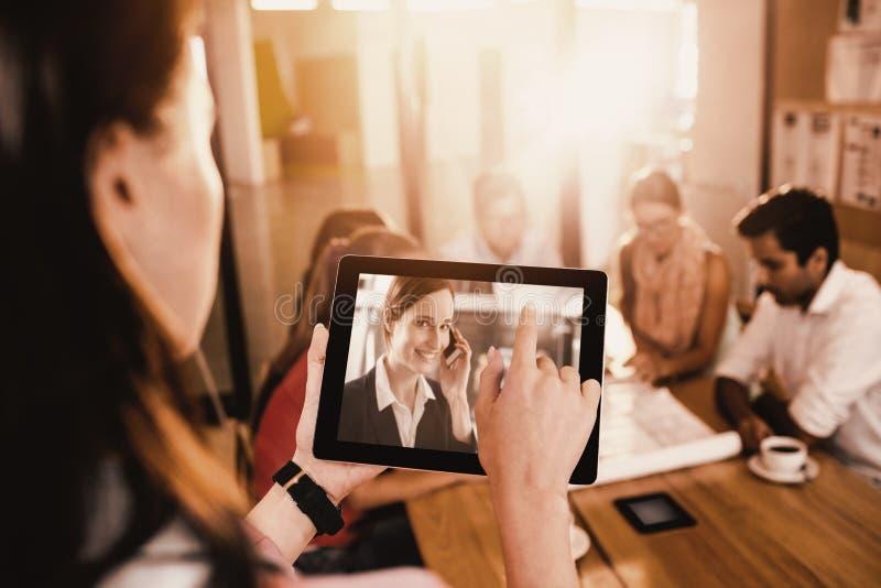 Immagine composita della donna di affari che per mezzo della compressa digitale mentre discutendo con i colleghi fotografia stock