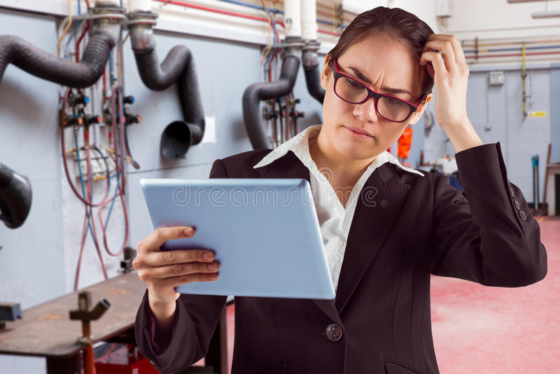 Immagine composita della donna di affari di pensiero che esamina il pc della compressa fotografia stock