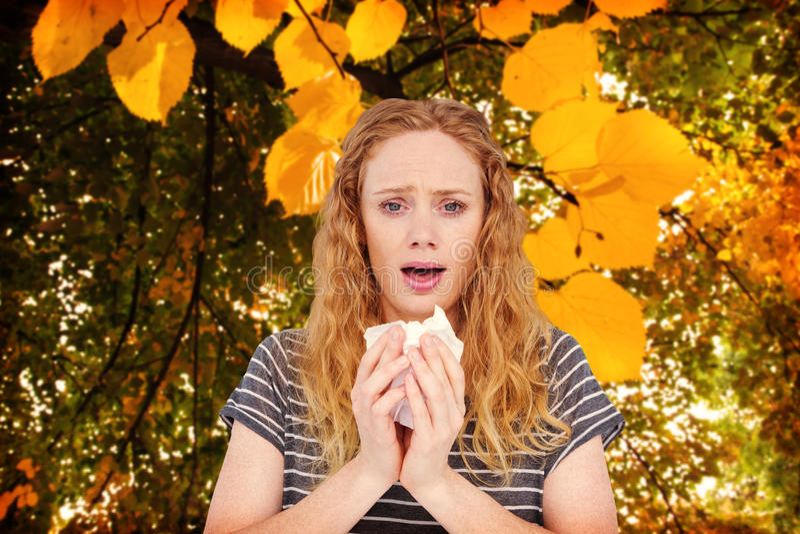 Immagine composita della donna malata che starnutisce in un tessuto fotografia stock