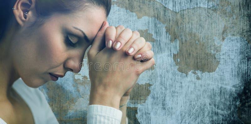 Immagine composita della donna pacifica che prega con prender per manosi e degli occhi chiusi immagini stock