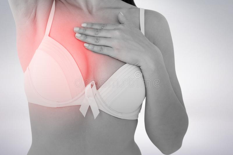 Immagine composita della donna in reggiseno con il nastro di consapevolezza del cancro al seno fotografie stock