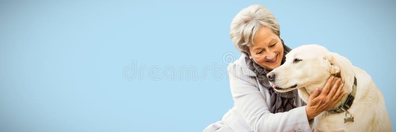 Immagine composita della donna senior che tiene un cane fotografie stock libere da diritti
