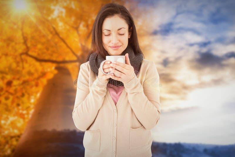 Immagine composita della donna sorridente che odora bevanda calda immagine stock libera da diritti