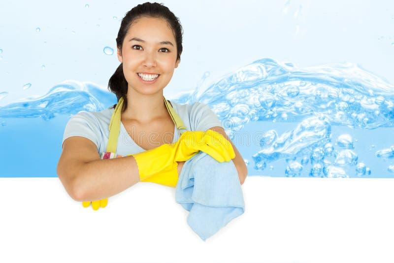 Immagine composita della donna sorridente che si appoggia la superficie di bianco fotografia stock libera da diritti