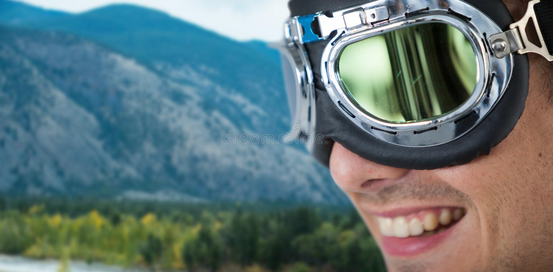 Immagine composita della fine su degli occhiali di protezione d'uso dell'aviatore dell'uomo felice fotografia stock