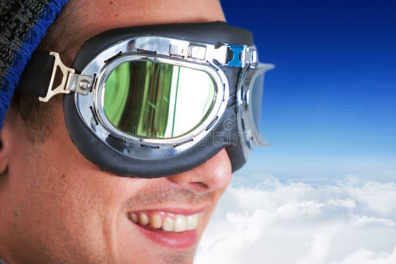 Immagine composita della fine su degli occhiali di protezione d'uso sorridenti dell'aviatore dell'uomo fotografia stock