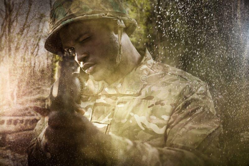 Immagine composita della fine su del soldato che tende con il fucile fotografie stock libere da diritti