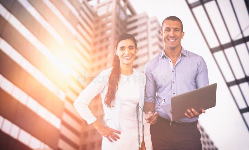 Immagine composita della gente di affari sorridente che per mezzo di un computer portatile immagine stock libera da diritti