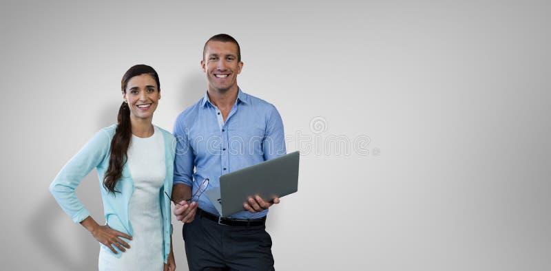 Immagine composita della gente di affari sorridente che per mezzo di un computer portatile immagini stock libere da diritti
