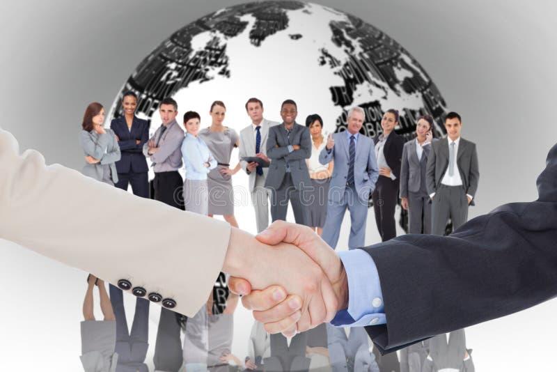 Immagine composita della gente di affari sorridente che stringe le mani mentre esaminando la macchina fotografica fotografia stock