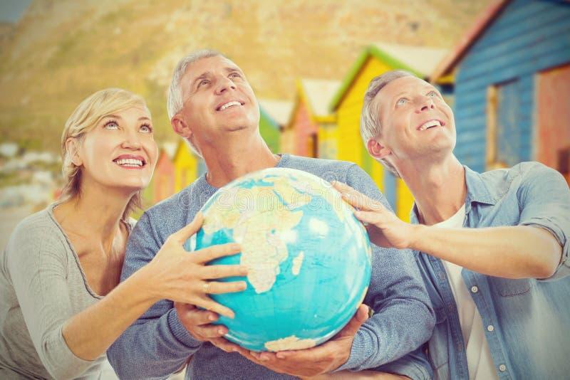 Immagine composita della gente sorridente che cerca mentre tenendo globo immagini stock libere da diritti