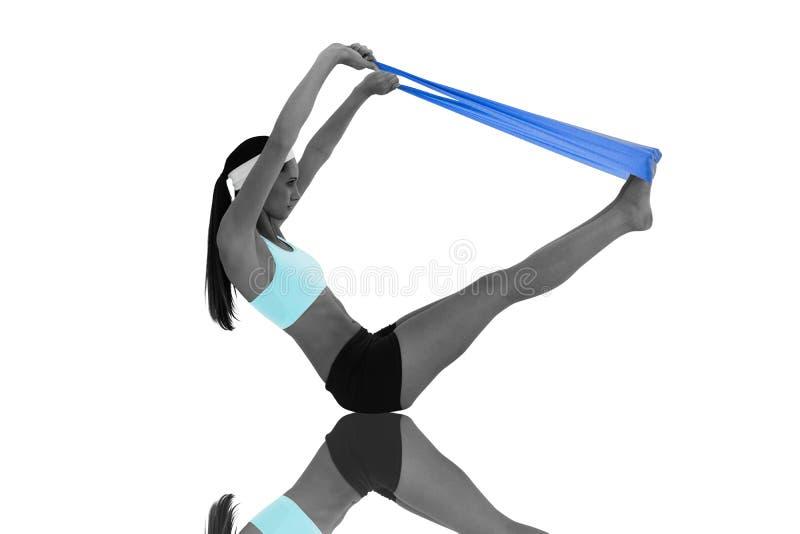 Immagine composita della giovane donna di misura che si esercita con una cinghia blu di yoga fotografie stock