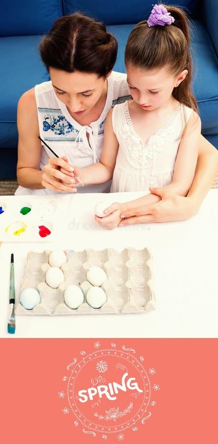 Immagine composita della madre e della figlia che dipingono le uova di Pasqua fotografia stock libera da diritti