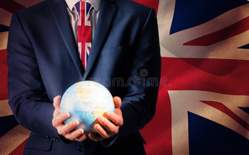 Immagine composita della mano dell'uomo d'affari che tiene globo terrestre fotografia stock