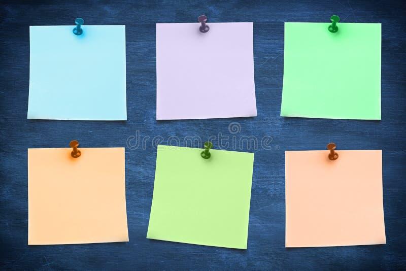Immagine composita della nota appiccicosa blu con la puntina da disegno fotografia stock